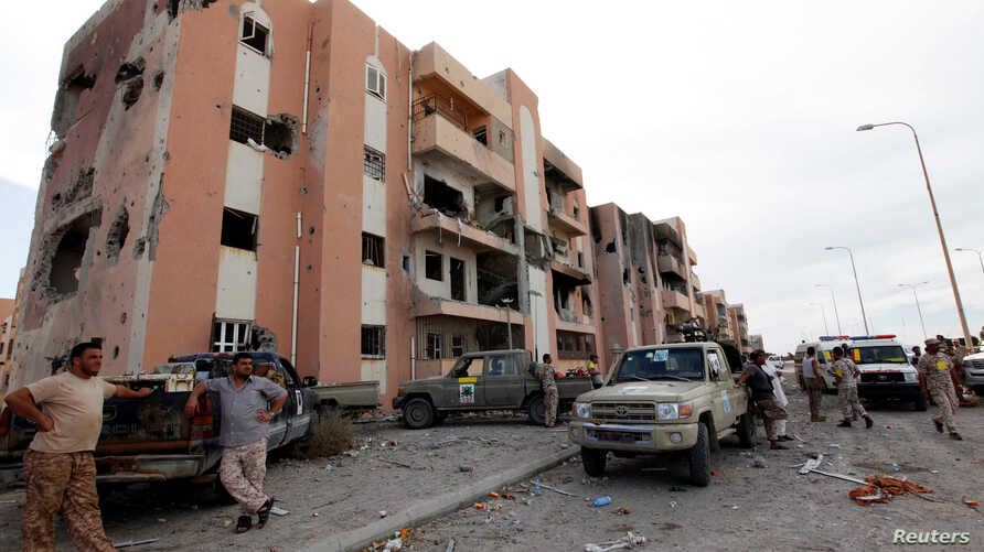 Libyan forces allied with the U.N.-backed government gather in front of ruined buildings at the eastern frontline of fighting with Islamic State militants, in Sirte's neighborhood 650, Libya, Oct. 21, 2016. The six-month fight to oust Islamic State h