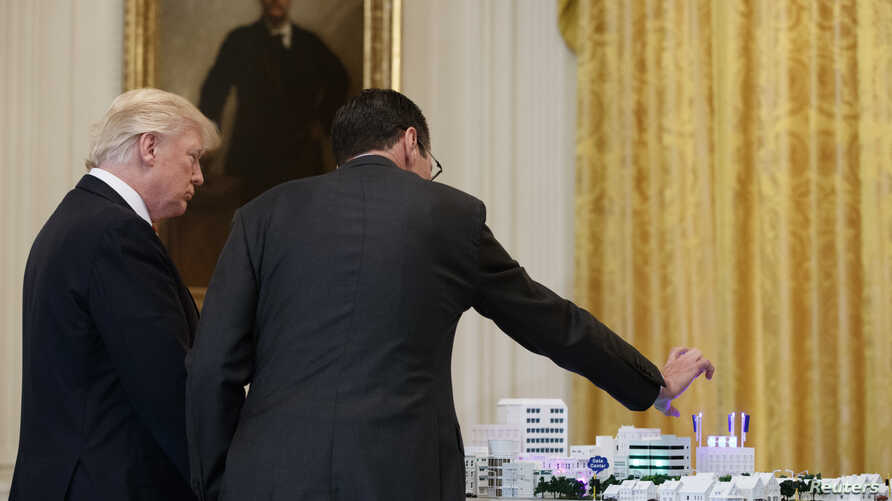 "AT&T CEO Randall Stephenson, right, demonstrates 5G technology to President Donald Trump during the ""American Leadership in Emerging Technology"" event in the East Room of the White House, June 22, 2017, in Washington."