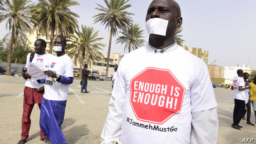 """People with a white paper covering their mouth and a t-shirt reading """"enough is enough"""" demonstrate in Dakar on April 22, 2016, against the alleged human rights violations in Gambia."""