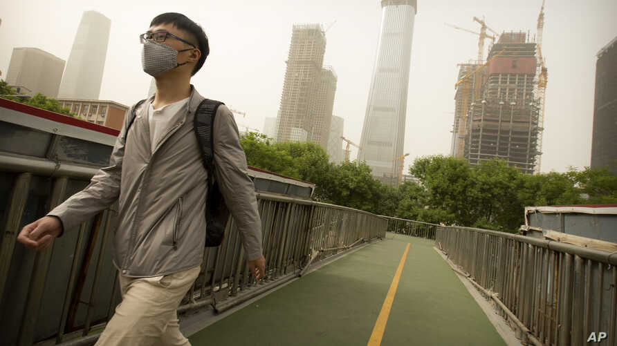 A man wears a face mask as he walks across a pedestrian bridge during a dust and sand storm in Beijing, May 4, 2017.