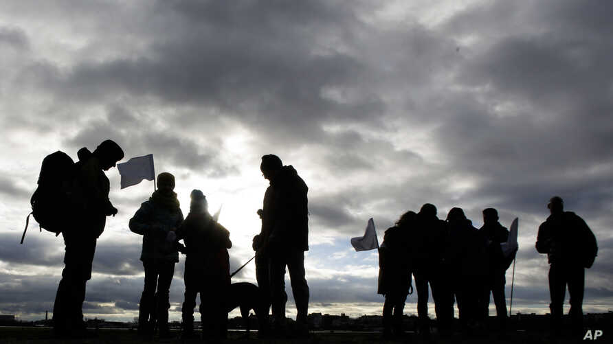 Demonstrators with white flags silhouette in front of a cloudy sky as they wait for the launch of the Civil March for Aleppo at the air field of the former airport Tempelhof in Berlin, Dec. 26, 2016.