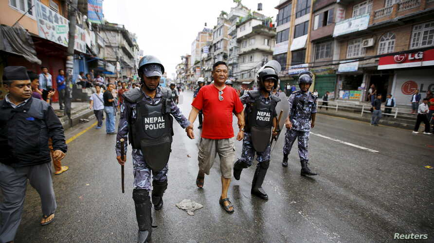 Nepalese police personnel detain a protester (C) during a general strike organized by the Nepal Federation of Indigenous Nationalities (NEFIN) demanding autonomous regions based on ethnicity to be drafted into the new constitution in Kathmandu, Nepal
