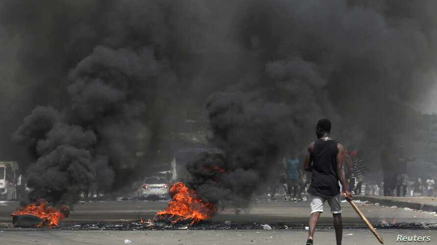 Anti-Gbagbo protesters block a street with burning tires after former Ivory Coast President Laurent Gbagbo was acquitted of all charges at the ICC war crimes court, in Abidjan's Abobo neighborhood, Ivory Coast, Jan. 16, 2019.