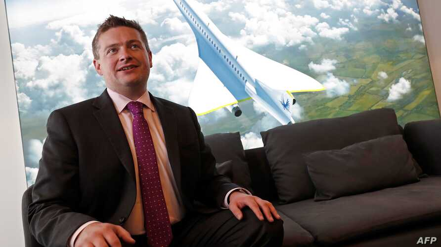 Boom Supersonic co-founder, Blake Scholl, poses in front of an artists impression of his company's proposed design for an supersonic aircraft, dubbed Baby Boom, at the Farnborough Airshow, south west of London, on July 18, 2018.