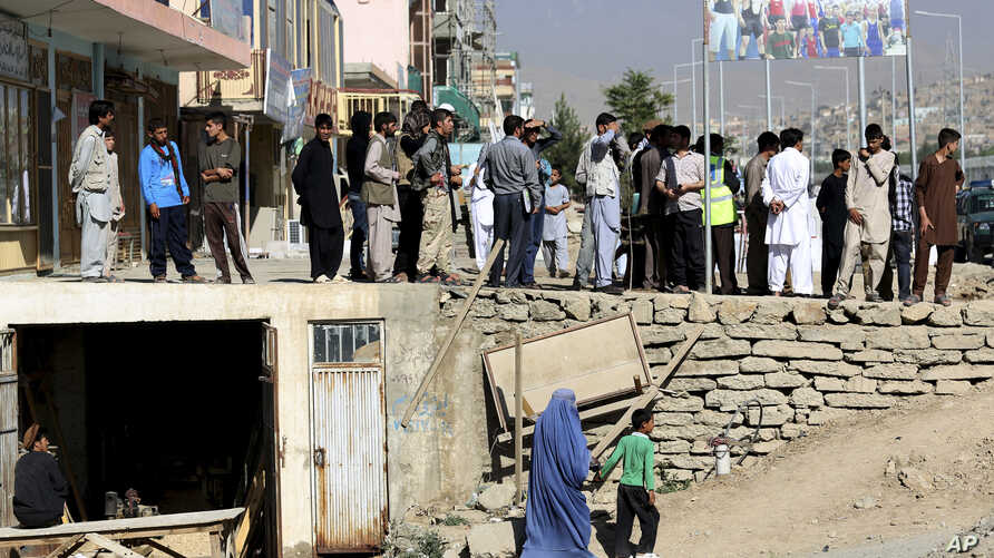 People look at the site of a suicide attack in the deputy counter narcotic compound in Kabul, Afghanistan, Tuesday, July 22, 2014. Gen. Mohammad Ayoub Salangi deputy interior said on Tuesday that four security guards were killed and six others were w