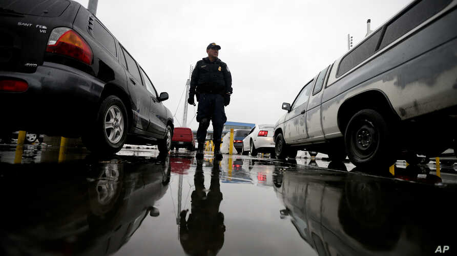 FILE - An Immigration and Customs Enforcement agent watches cars as they wait to enter the United States from Tijuana, Mexico, through the San Ysidro port of entry in San Diego, Dec. 3, 2014..