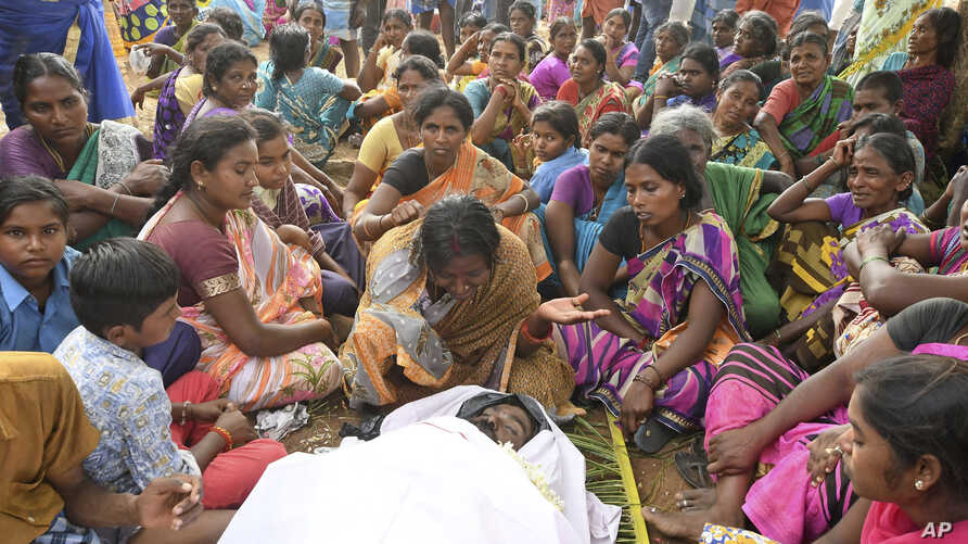 A woman cries near the body of her husband who died of suspected food poisoning at Bidarahalli, near Sulawadi village in Chamarajnagar district of Karnataka state, India, Saturday, Dec. 15, 2018.
