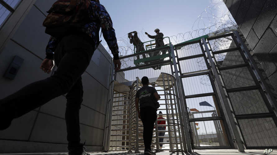 Marines install concertina wire, above, as pedestrians leave the United States for Mexico at the San Ysidro port of entry, Nov. 16, 2018, in San Diego.