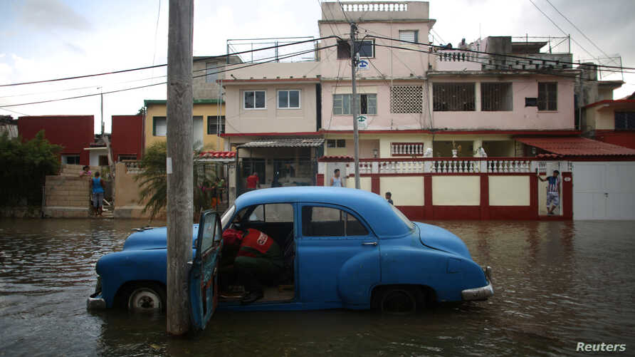 A man tries to start the engine of a vintage car in a flooded street in Havana, Cuba, January 23, 2017.