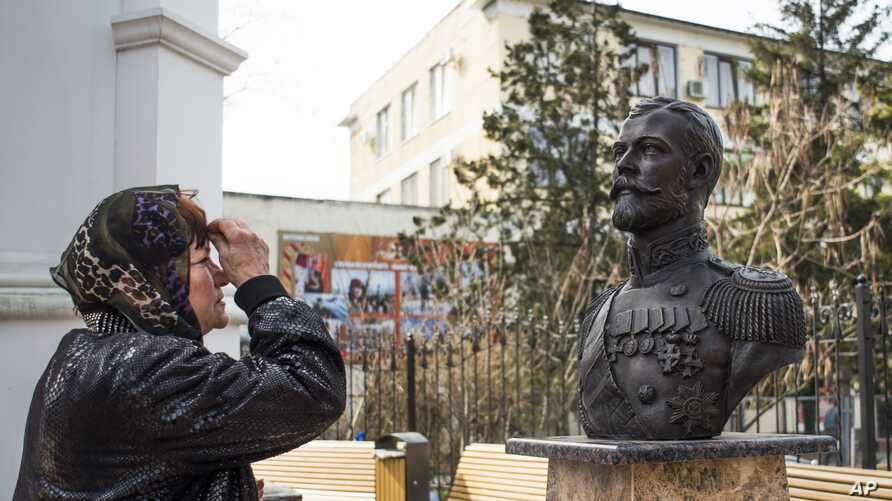 A woman prays at a bust of the last Russian Czar Nicholas II placed near the Crimean prosecutor's office, foreground, in Simferopol, Crimea, March 6, 2017.