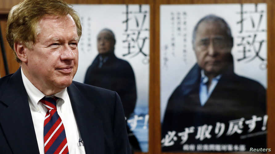 Robert King, U.S. special envoy for North Korean human rights issues, stands in front of campaign posters of Japan's abduction issue during a meeting with Japan's Minister-in-Charge of the Abduction Issue and head of the national public safety commis