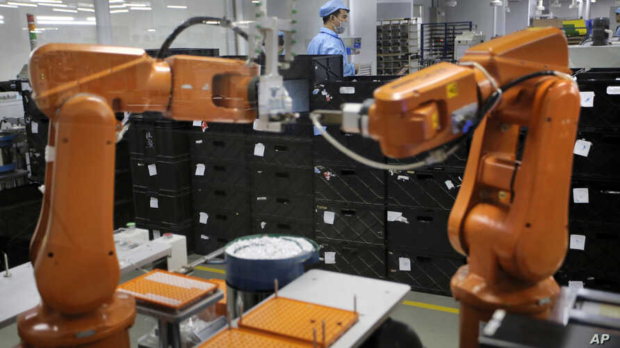 A Chinese worker is seen behind orange robot arms at Rapoo Technology factory in the southern Chinese industrial boomtown of Shenzhen, Aug. 21, 2015. Automation could wipe out two thirds of jobs in some countries, the World Bank warns.