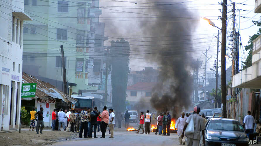 Protesting Muslim youths stand next to burning tires in Mombasa, Kenya after Aboud Rogo, a Muslim cleric facing terror-related charges, was shot dead, Monday Aug. 27, 2012..