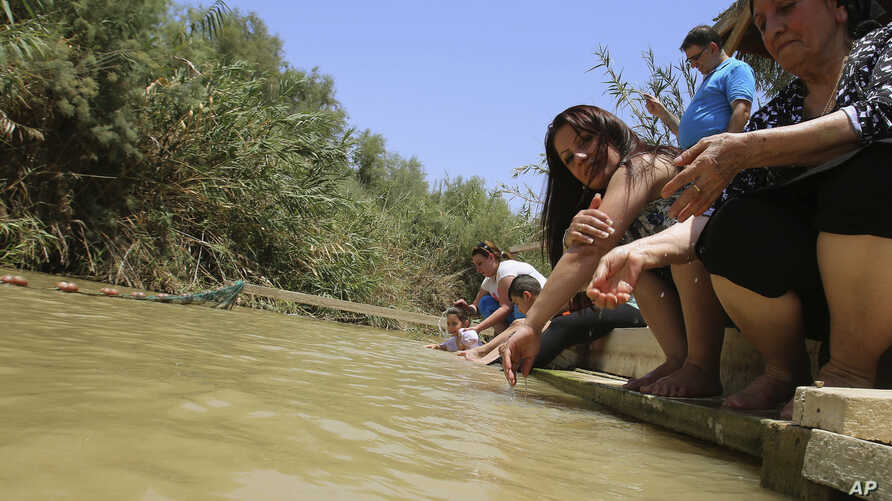 FILE - In this July 6, 2015, photo, Jordanian Christians pour water over themselves at what they believe to be Jesus' baptismal area on the eastern bank of the Jordan River in South Shuna, Jordan.