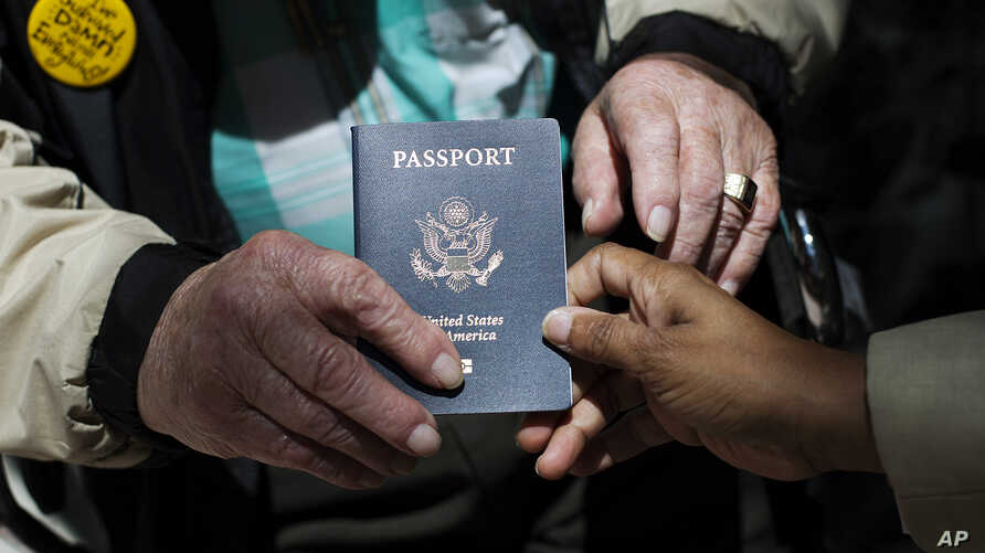 File - Outside a Department of State office, a World War II veteran hold his U.S. passport, June 2, 2014.
