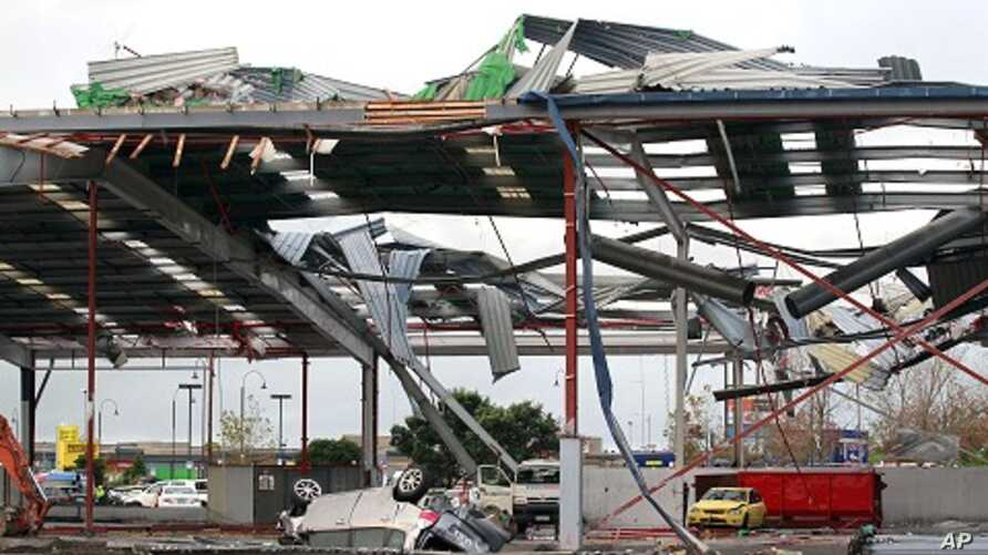 A car in a mall parking garage is overturned in front of a large building after a tornado ripped through the suburb of Albany in Auckland May 3, 2011.
