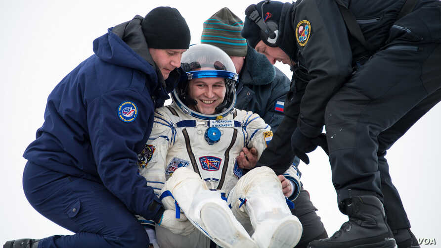 Expedition 38 Flight Engineer Sergey Ryazanskiy of the Russian Federal Space Agency, Roscosmos, is helped out of the Soyuz Capsule just minutes after he and Commander Oleg Kotov of the Roscosmos, and, Flight Engineer Mike Hopkins of NASA, landed in t
