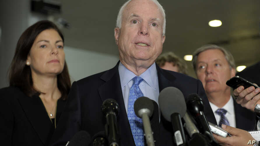 Sen. John McCain, R-Ariz., ranking Republican on the Senate Armed Services Committee, center, flanked by fellow committee members, Sen. Kelly Ayotte, R-N.H., left, and Sen. Lindsey Graham, R-S.C., right, speaks on Capitol Hill in Washington, Nov. 27,