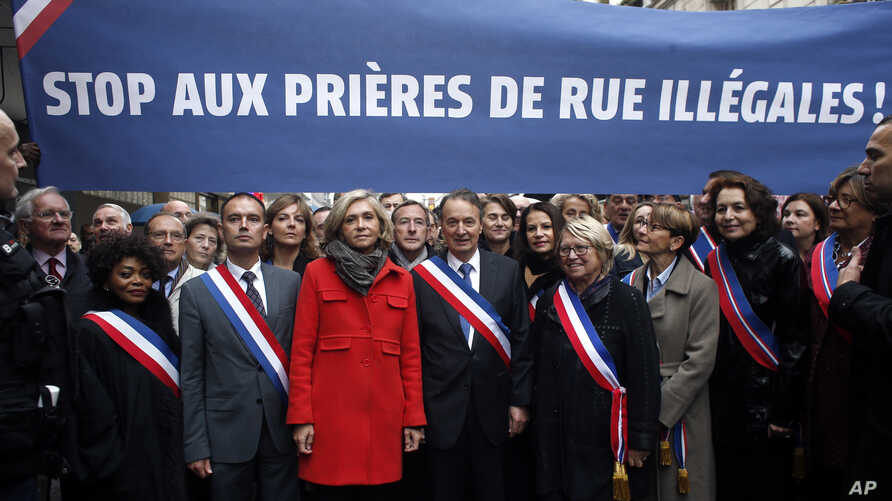 Clichy la Garenne's mayor Remi Muzueau, center right, and President of the Regional Council of the Ile-de-France region Valerie Pecresse, center left, demonstrate against Muslim street prayers, in the Paris suburb of Clichy la Garenne, Friday, Nov. 1