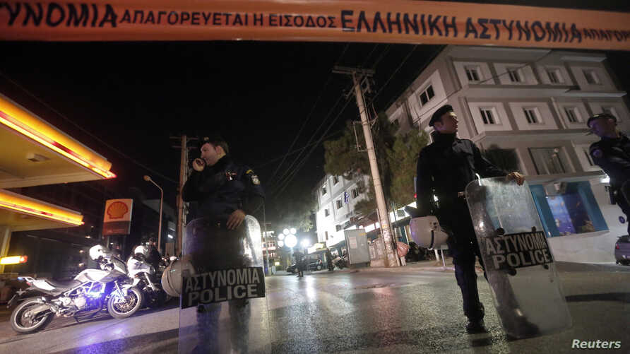 Police officers stand guard near the local offices of the neo-Nazi Golden Dawn party, following a shooting, in a northern suburb of Athens, Nov. 1, 2013.