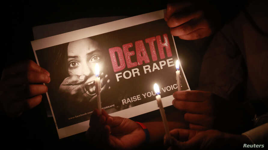 People hold a placard during a candlelight vigil in support of women safety in Mumbai, India, Dec. 20, 2012.