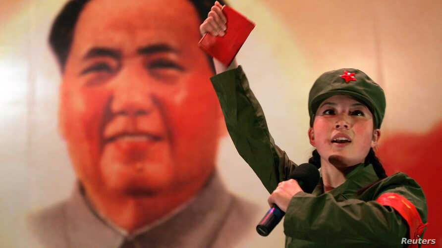 """FILE - A Chinese, dressed as a Red Guard and holding a """"Little Red Book"""" (quotations of Chairman Mao), performs in front of a portrait of the late Chairman Mao Zedong at a restaurant named """"Red Classic"""" in Beijing."""