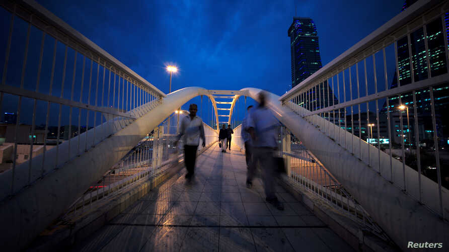Workers cross the pedestrian bridge during rush hour from Bahrain Financial Harbour to downtown Manama, during the early evening hours in Manama, Bahrain, Nov.12, 2018.