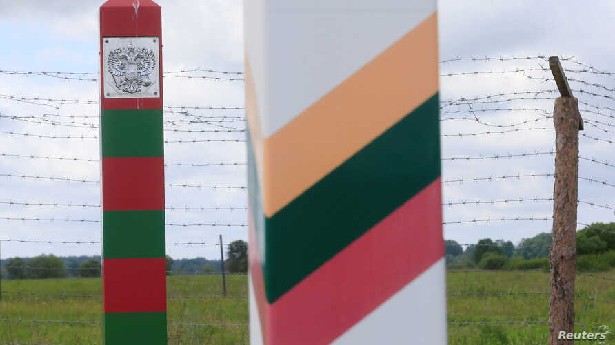 Lithuanian (R) and Russian border signs are seen near the Sudargas border crossing point with Russia in Ramoniskiai, Lithuania, June 5, 2017.