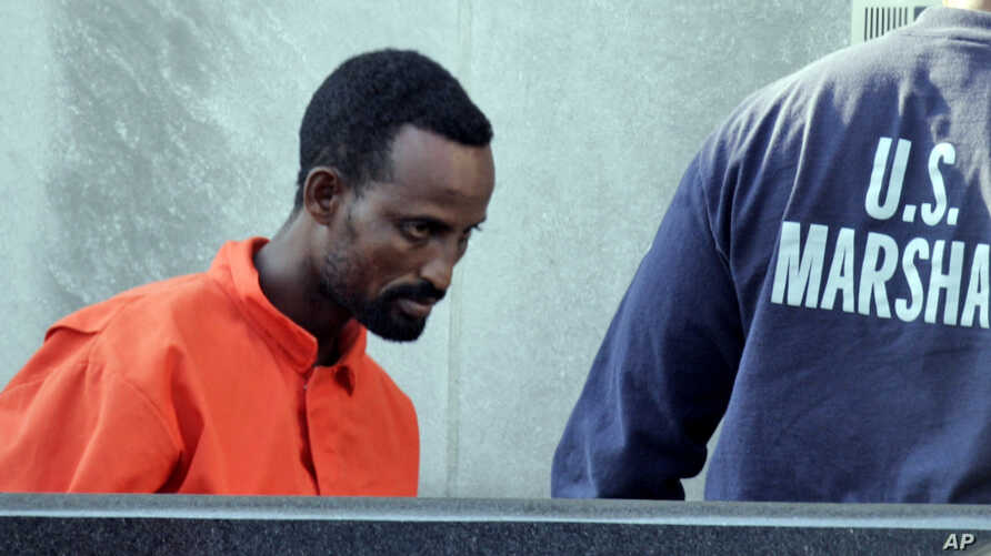 FILE - A suspected pirate from Somalia is escorted into federal court by U.S. Marshals in Norfolk, Virginia, April 23, 2010. Three pirates received sentences on Tuesday.
