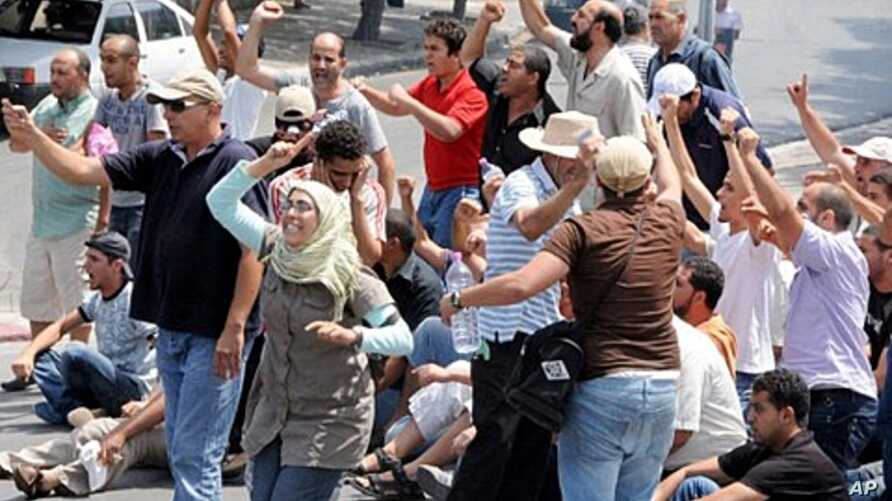 Demonstrators shout slogans as they clash with Tunisian security forces in La Kasbah square,  July 15, 2011
