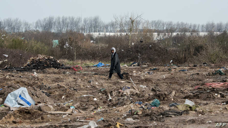 "A man walks among remains of taken down shelters during the dismantling of the southern part of the so-called ""Jungle"" migrant camp in Calais, northern France, March 10, 2016."