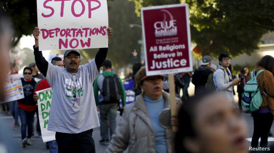FILE - People hold signs as they gather outside a Federal Building while protesting against Immigration and Customs Enforcement (ICE) raids on Central American refugees in Los Angeles, California, Jan. 26, 2016.