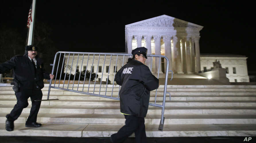 Supreme Court police officers move a barricade in front of the U.S. Supreme Court, Feb. 19, 2016 in Washington.