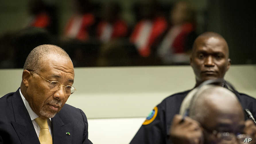 Former Liberian President Charles Taylor, left, waits for the start of his appeal judgement at the Special Court for Sierra Leone (SCSL) in Leidschendam, near The Hague, Netherlands, Sept. 26, 2013.