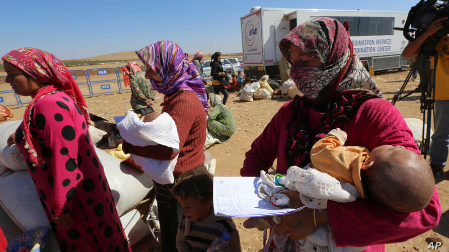 Narin Mustafa, 26, center, holds her 10-day-old baby girl Merva as thousands of new Syrian refugees from Kobani arrive at the Turkey-Syria border crossing of Yumurtalik near Suruc, Turkey, Wednesday, Oct. 1, 2014. U.S.-led coalition airstrikes target