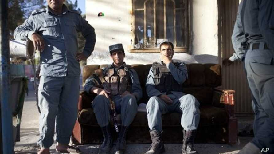 Afghan national policemen take a brief break at a checkpoint in Lashkar Gah in volatile southern Helmand province, Oct 23, 2012.
