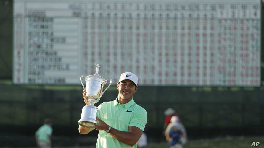 Brooks Koepka poses with the winning trophy after the U.S. Open golf tournament, June 18, 2017.