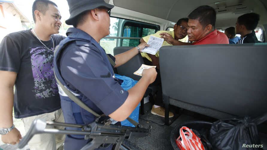 Malaysian police personnel checks identity of passengers on a road leading to Kampung Tanduo, where Malaysian troops stormed the camp of an armed Filipino group, in Lahad Datu, Sabah state, Mar. 8, 2013