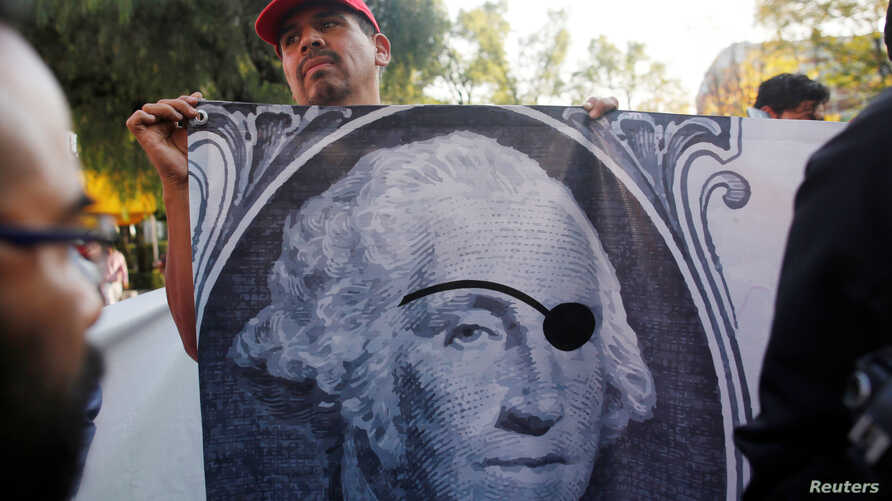 A union worker holds a banner during a protest against NAFTA negotiations outside where the fifth round of NAFTA talks involving the United States, Mexico and Canada in Mexico City, Mexico, Nov. 17, 2017.