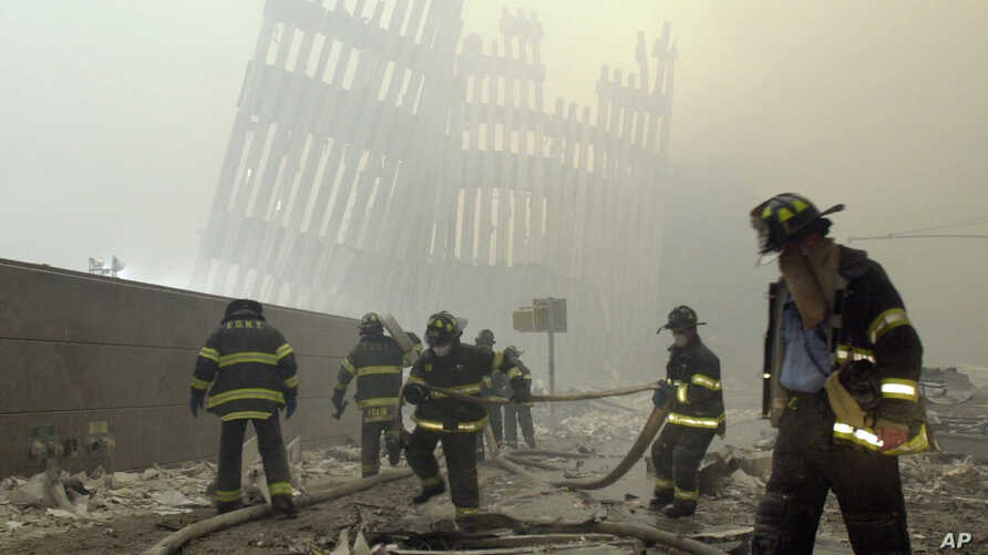 FILE - With the skeleton of the World Trade Center twin towers in the background, New York City firefighters work amid debris on Cortlandt Street after the terrorist attacks of Sept. 11, 2001.