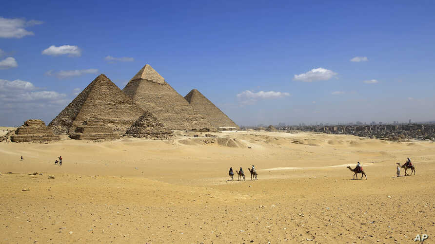 FILE - In this April 9, 2015 image tourists ride camels at the historical site of the Giza Pyramids in Giza, near Cairo, Egypt. Republican presidential candidate Ben Carson says it's still his belief the great pyramids Egypt were built by the Bibli...