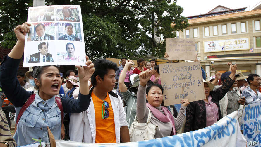 A supporter (L) holds up portraits of opposition lawmakers of the Cambodia National Rescue Party (CNRP) who were charged with leading an insurrection movement during a rally in front of Phnom Penh Municipality Court in Phnom Penh, Cambodia, July 17,