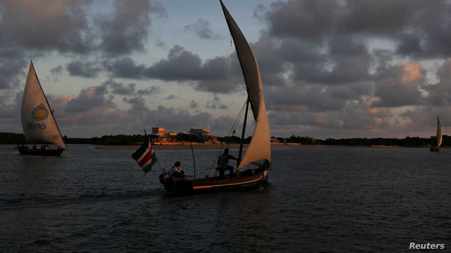 FILE - Traditional dhows sail by close to the island of Lamu, Kenya, Nov. 8, 2017. Lamu, a United Nations World Heritage Site, is also the site of a planned, controversial coal-fired power plant.