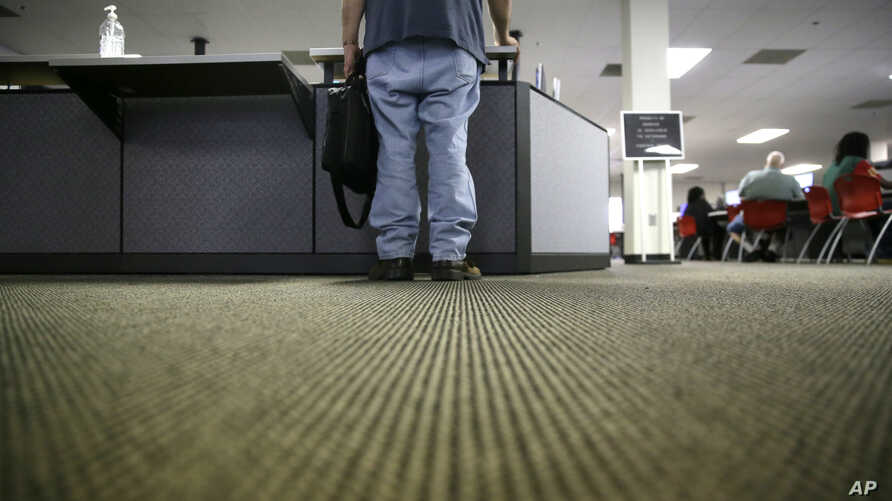 FILE - A lone job seeker checks in at the front desk of the Texas Workforce Solutions office in Dallas,  March 10, 2017.