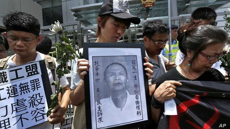 Protesters mourn the death of Chinese labor activist Li Wangyang, seen in picture at center, during a protest outside the Chinese central government's liaison office, in Hong Kong  June 7, 2012.
