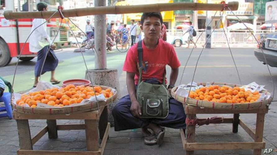 Boy sells fruit on sidewalk in Rangoon, Burma, December 5, 2011