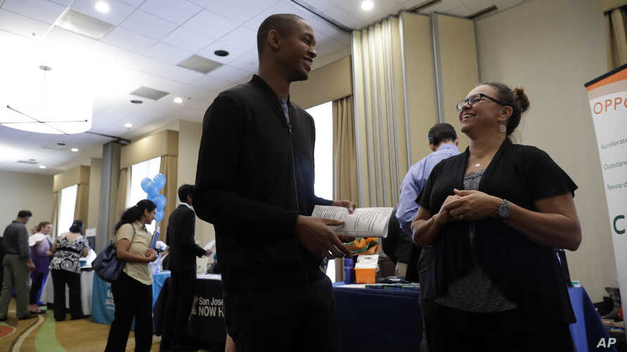 FILE - Kathy Tringali, right, a recruiter for Big 5 Sporting Goods, talks to job seeker Jarrell Palmer during a job fair, in San Jose, Calif., Aug. 24, 2017.