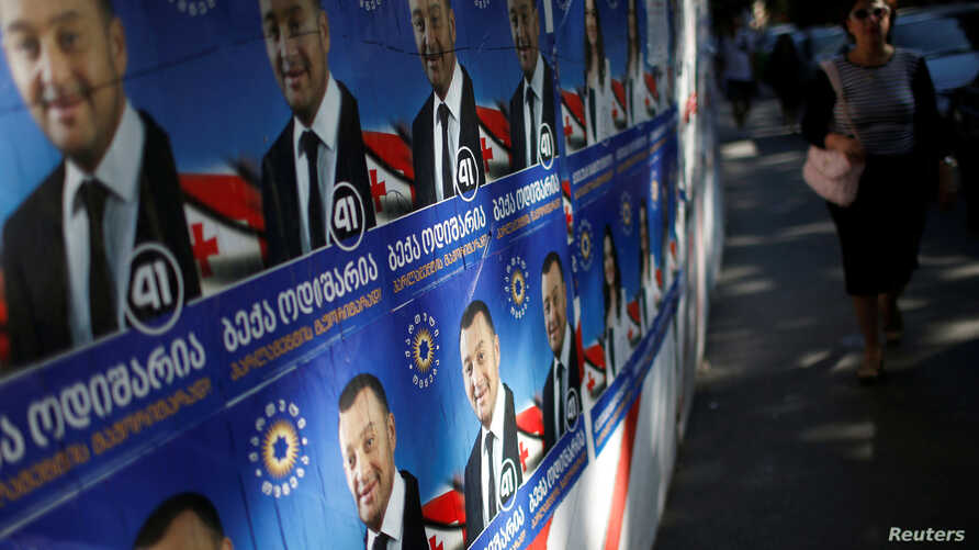 A woman walks past election posters ahead of the parliamentary elections in Tbilisi, Georgia, Oct. 6, 2016.