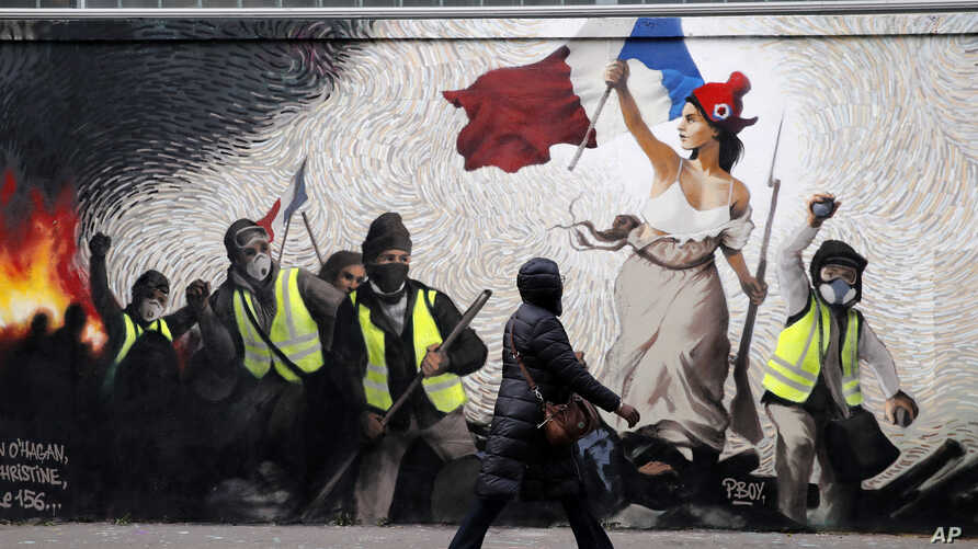 """A woman passes by a mural by street artist PBOY depicting Yellow Vest (gilets jaunes) protestors inspired by a painting by Eugene Delacroix, """"La Liberte guidant le Peuple"""" (Liberty Leading the People), in Paris, Thursday, Jan. 10, 2019."""