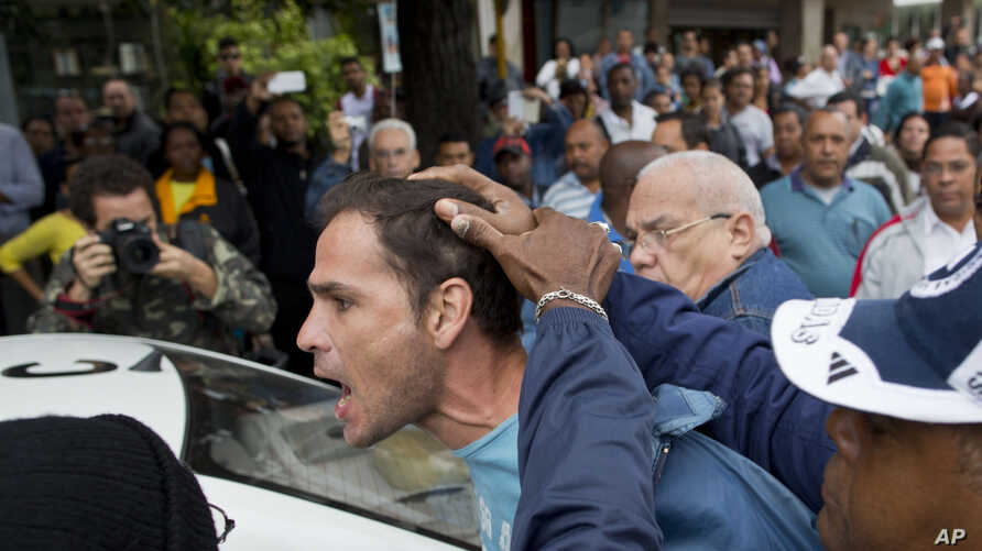 FILE - An opposition activist is detained by Cuban security officers ahead of a march marking International Human Rights Day in Havana, Cuba, Dec. 10, 2014.